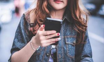 primo piano di una donna di bellezza in giacca di jeans che usa lo smartphone? foto