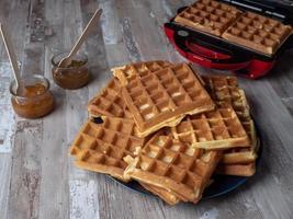 waffle belgi impilati uno sopra l'altro e su un piatto foto
