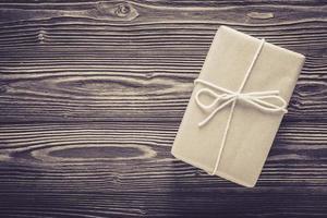 sopra pacchetto confezione regalo e corda su sfondo texture tavolo in legno. foto