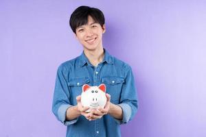 ritratto di uomo asiatico in camicia blu in posa su sfondo viola foto