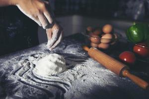 donne asiatiche che preparano una pizza, sul tavolo della cucina foto