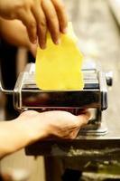 chef che fa la pasta con la macchina, pasta fresca fatta in casa foto