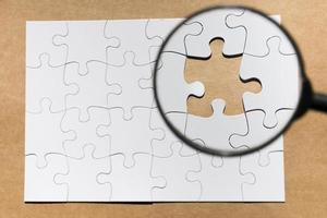 lente d'ingrandimento su un puzzle mancante foto