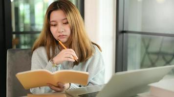 donna adolescente che tiene matita e taccuino gesto serio con il computer portatile. foto