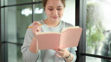 una donna asiatica adolescente con una penna sta vicino alla finestra. foto