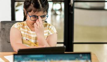 la ragazza asiatica del bambino mette la mano sugli occhiali e sembra stanca dallo studio. foto