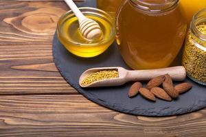 miele con mestolo di miele in legno su tavola di legno foto