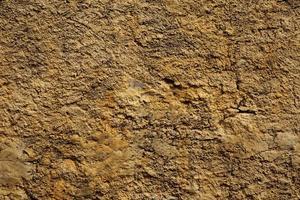 muro di pietra giallo in piccole crepe foto