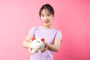 Ritratto di ragazza con salvadanaio in mano, isolato su sfondo rosa foto