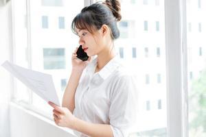 ritratto di giovane donna d'affari in piedi vicino alla finestra e fare telefonate con il suo partner foto