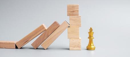blocchi di legno o domino che cadono sulla figura del re degli scacchi d'oro. affari, gestione del rischio, soluzione, regressione economica, assicurazione foto