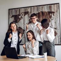 un gruppo di uomini d'affari che lavorano in un ufficio in una riunione congiunta fa un gesto vincente foto