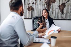 attraente donna d'affari in ufficio a discutere attivamente del progetto con il suo collega foto