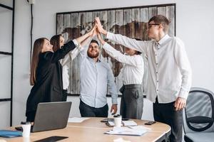 uomini d'affari felici che mostrano il lavoro di squadra e danno cinque dopo aver firmato un accordo o un contratto con i partner negli interni dell'ufficio. persone felici che sorridono. accordo o concetto di contratto. - Immagine foto