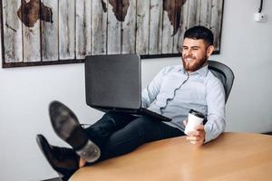 bravo ragazzo con la barba seduto a un tavolo, mettendo i piedi sul tavolo, bevendo caffè e lavorando al computer foto