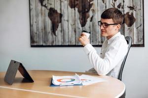 giovane uomo d'affari con gli occhiali che beve caffè e guarda le notizie sul tablet foto