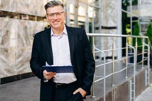 felice uomo d'affari senior con gli occhiali in possesso di un documento e guardando la telecamera - immagine foto