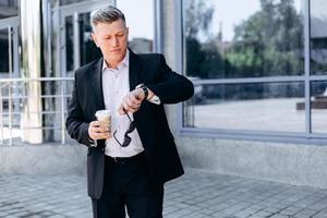 uomo d'affari senior che controlla il tempo sull'orologio in mano in città, con in mano occhiali da sole e bicchiere da caffè foto
