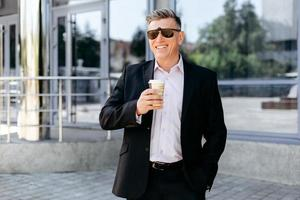 ritratto di uomo d'affari anziano in piedi sul marciapiede con in mano una tazza di caffè e sorridente. - Immagine foto