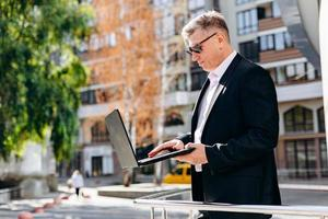 uomo d'affari senior serio in occhiali da sole che tiene un computer portatile e che lavora in esso all'aperto. - Immagine foto