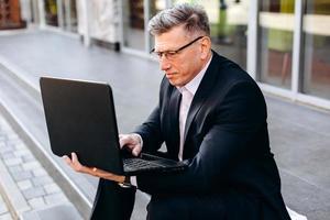 ritratto di uomo anziano in tuta seduto sul marciapiede e in possesso di un computer portatile e digitando all'aperto. - Immagine foto