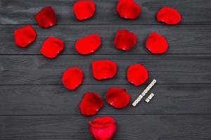fondo del pavimento strutturato in legno scuro ricoperto di petali di rose rosse. primo piano, vista dall'alto, copia spazio foto