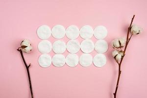 ramo di cotone e tamponi di cotone sdraiato su uno sfondo rosa. foto