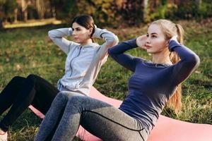 lavoro di squadra. esercizio swing press due belle ragazze foto
