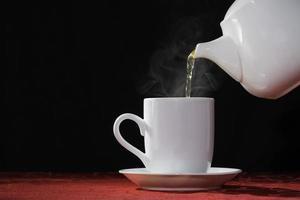 versando la bevanda calda del tè foto