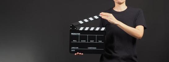mano che tiene ciak giallo e nero o uso di ardesia cinematografica nella produzione di video, film, industria cinematografica su sfondo nero. foto