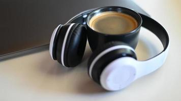 tazza da caffè con laptop e cuffie posizionati su un tavolo in un bar, posto tazza da caffè in cuffia. foto