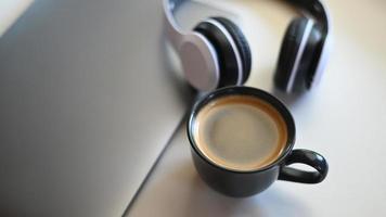 vista dall'alto di una tazza da caffè con laptop e cuffie posizionate su un tavolo in un bar. foto