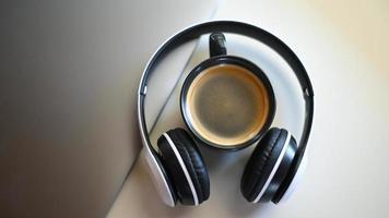 vista dall'alto di una tazza da caffè con laptop e cuffie posizionata su un tavolo in un bar, una tazza da caffè in cuffia. foto