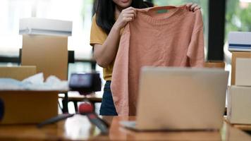 le donne mostrano la vendita di camicie online da casa. usa il suo laptop per vendere sui social media. concetti di acquisto online. foto