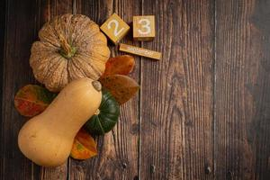 zucca, foglia d'acero e calendario posizionati su pavimento in legno, ciao concetto di settembre. foto