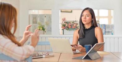 la giovane donna tiene uno smartphone in mano e un laptop con tablet sul tavolo. lei e la sua amica stanno preparando un progetto per presentare un cliente. foto