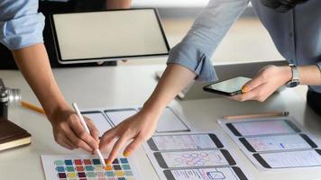 Il team di professionisti di ux,ui con smartphone e tablet sta progettando nuovi progetti. foto