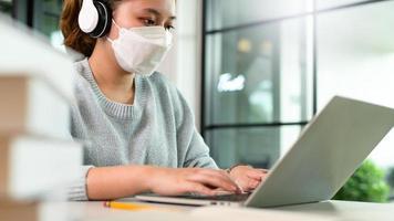 una giovane donna che indossa le cuffie e una maschera sta usando un laptop. foto