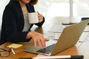 una donna in giacca e cravatta preme la mano sulla tastiera di un laptop e tiene il caffè con l'altra mano. foto