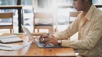 giovane freelance che utilizza un computer portatile per creare il progetto del cliente, si siede online lavorando in un bar, concetti di business. foto