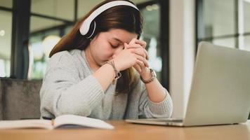 giovane ragazza asiatica che si tiene per mano e a testa in giù espressione stanca mentre studia online con il computer portatile. foto
