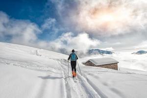 una ragazza fa sci alpinismo foto