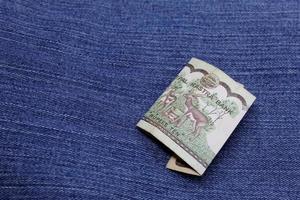 banconota nepalese da dieci rupie tra tessuto denim blu foto