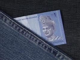 banconota malese di un ringgit tra tessuto denim blu foto