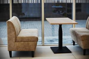 mobili da caffè beige morbidi vicino alla parete della finestra di vetro foto