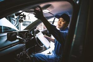 meccanico che tiene appunti e controlla all'interno dell'auto per il veicolo di manutenzione dall'ordine di reclamo del cliente nel garage dell'officina di riparazione auto. servizio di riparazione. occupazione delle persone e lavoro aziendale. tecnico automobilistico foto
