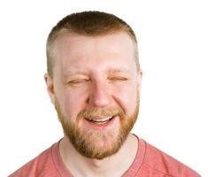 uomo barbuto divertente con gli occhi socchiusi foto