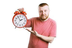 uomo con una sveglia rossa in mano foto