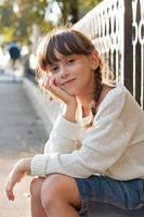 bella ragazza in un maglione bianco e calzoni foto