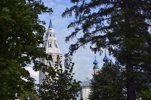 cupole della chiesa con croci contro il cielo blu. tempio di pietra bianca tra gli alberi del villaggio. foto